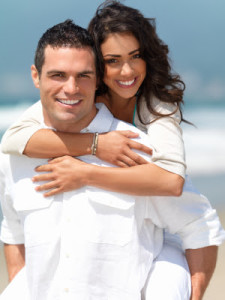Portrait of a happy young couple having fun on the beach. Couple enjoying a summer vacation.